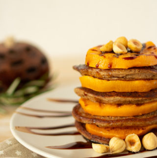 Vegan oatmeal pancakes with grilled persimmons garnished with hazelnuts and coconut syrup